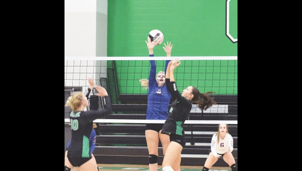 Middle hitter Chloe Costello goes up for a block against the Green Devils in last Tuesday night's 3-0 (25-8, 25-10, 25-11) loss in Osage. Costello is now third on the team with 57 kills and second with 23 blocks.