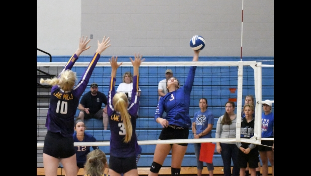 N-K's Marli Backhaus gets the ball past two Lake Mills defenders in last Saturday's tournament action in Manly. Backhaus, a senior, leads the team on the year with 38 kills and 24 blocks.